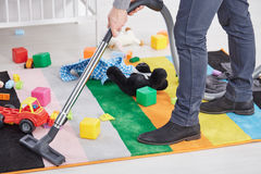 Man vacuuming child`s room. Close up of man vacuuming messy child`s room Stock Images
