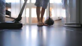 Man vacuuming the floor stock footage