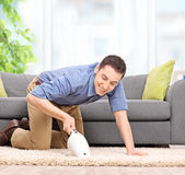 Man vacuuming with a handheld vacuum cleaner Royalty Free Stock Photography