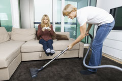 Man vacuuming while woman play video game in living room at home. Man vacuuming while women play video game in living room at home Stock Photos