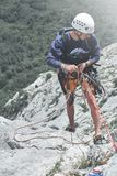 Man vaggar klättraren på överkanten av klippan och belägger en partner Fotografering för Bildbyråer