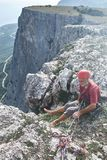 Man vaggar klättraren sitter på överkanten av klippan och belägger en partner Fotografering för Bildbyråer