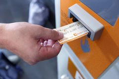 A man validating ticket in a punching machine for the train. Barcelona, Spain. Stock Photos