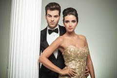 Man van het manier de elegante paar in smoking en vrouw dichtbij kolom Royalty-vrije Stock Afbeelding