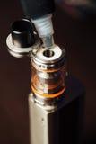 Man in a vape shop is filling a special liquid in e-cigarette. Steam cigarette stock image