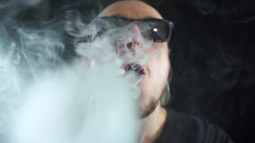 Man vaping big ring of steam and sends it to the camera with in slow motion