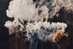 Man vaping an electronic cigarette. Vaping man wearing a hat, holding up a mod, obscured behind a cloud of vapor. Processed with VSCO c2 preset Royalty Free Stock Photos