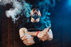 Man vaping an electronic cigarette. Vaping man wearing a hat, obscured behind a cloud of vapor stock photo
