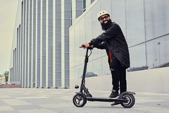 A man vaping and riding by electric scooter. Bearded hipster male vaping and riding by electric scooter over modern building royalty free stock image