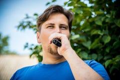 Man vaping. Young man vaping outdoors closeup portrait stock photography