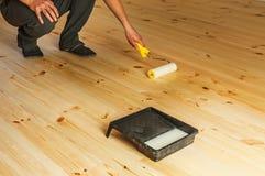 Man varnishing floor Stock Photo