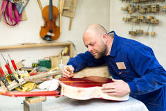 Man varnishing a guitar Royalty Free Stock Photos