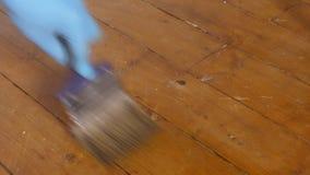 Man varnishing a wooden floor stock footage