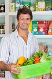 Man With Vegetable Basket In Grocery Store. Portrait of happy mid adult man with vegetable basket in grocery store royalty free stock images