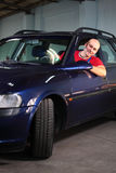 A man in vehicle. A car mechanic parking the vehicle in a motor repair car shop Royalty Free Stock Image
