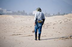 Man combing the beach with a metal detector Royalty Free Stock Images