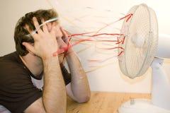 Man and ventilator. Colorful ribands Royalty Free Stock Photo