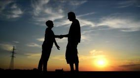 Man vergaderingsvrouw op de straat in zonsondergang en groet haar met een warme handdruk stock footage