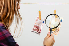 Man verify money cash. Currency exchange concept. Man worker check verify money cash. Payment hang on laundry line. Guy with loupe Stock Photo