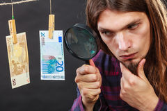 Man verify money cash. Currency exchange concept. Man worker check verify money cash. Payment hang on laundry line. Guy with loupe Stock Images