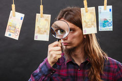Man verify money cash. Currency exchange concept. Man worker check verify money cash. Payment hang on laundry line. Guy with loupe Royalty Free Stock Image