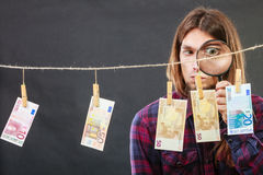 Man verify money cash. Currency exchange concept. Man worker check verify money cash. Payment hang on laundry line. Guy with loupe Royalty Free Stock Photography