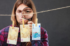 Man verify money cash. Currency exchange concept. Man worker check verify money cash. Payment hang on laundry line. Guy with loupe Royalty Free Stock Photo
