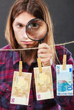 Man verify money cash. Currency exchange concept. Man worker check verify money cash. Payment hang on laundry line. Guy with loupe Stock Photos