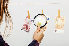 Man verify money cash. Currency exchange concept. Man worker check verify money cash. Payment hang on laundry line. Guy with loupe Royalty Free Stock Photos