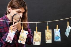 Man verify money cash. Currency exchange concept. Man worker check verify money cash. Payment hang on laundry line. Guy with loupe magnifying glass Royalty Free Stock Images