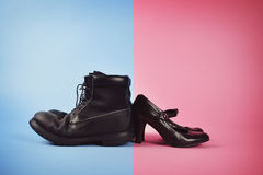 Man versus Woman's Power Struggle. A man's boots and woman's high heels are fighting against a blue and pink isolated background for a struggle or gender power Stock Image