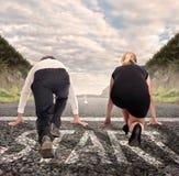 Man versus woman ready to run. Man versus women on a road ready to run Royalty Free Stock Image