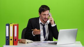 Man is very busy and annoyed on the work. Man unshaven is very busy and annoyed on the work, he is answers the phone call, taking notes on paper and then tearing stock video footage