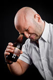 Man very emotionally looks at the bottom of the bottle Stock Photos