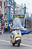 Man on Vespa scooter, Dam Square, Amsterdam. AMSTERDAM-AUG. 19. Man on Vespa scooter. Vespa (Italian for wasp) is an Italian brand scooters manufactured by Stock Photo