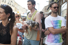 A man in a vest with a dachshund in his arms walking through the crowd on Sunday on Brick lane Stock Image