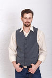 Man in vest and jeans. Young romantic man in vest and jeans. Men's fashion. Man put his hands on the belt stock photos
