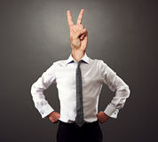 Man with victory sign. Instead of the head over dark background Stock Image
