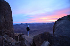 A man with a video camera meets dawn on Mount Moses, Egypt. Sinai peninsula Royalty Free Stock Photos