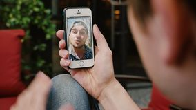 Man Video Chats with Male Friend on Smartphone. 10208 An over the shoulder shot of a young man video chatting outside with a male friend on his smartphone stock video footage