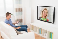 Man Video Chatting using Television Stock Photography