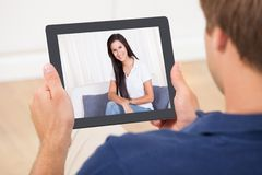 Man video chatting with woman. Cropped image of men video chatting with women at home royalty free stock images