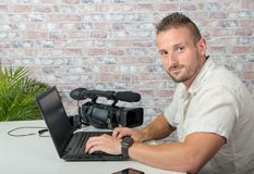 Man video editor with laptop and professional video camera. A man video editor with laptop and professional video camera royalty free stock photography