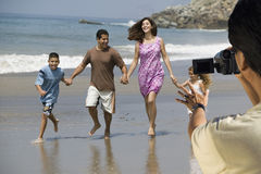 Man video recording happy Hispanic Latin family walking at beach Royalty Free Stock Image