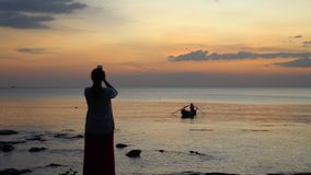 The man in the Vietnamese hat floats standing on the small boat. Silhouette at sunset. The woman photographs the boatman. On this video you can see as the small stock footage