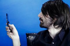 Man Viewing Cellphone Photo. A view of a young man with a full, black beard and long hair, holding up his cellphone screen to view a photo he has just taken Royalty Free Stock Photography