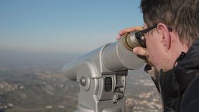 Man is viewing nature and landmarks by telescope stock video footage