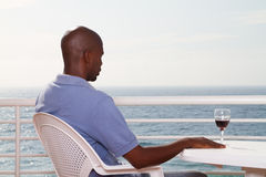 Man viewing seascape. Young african american man drinking wine and viewing seascape on balcony Royalty Free Stock Photo