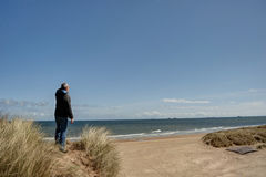 Man at a viewpoint overlooking a beach Royalty Free Stock Photography