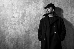 Man in vintage cap and coat standing near old wall. Black and white photo Royalty Free Stock Photos